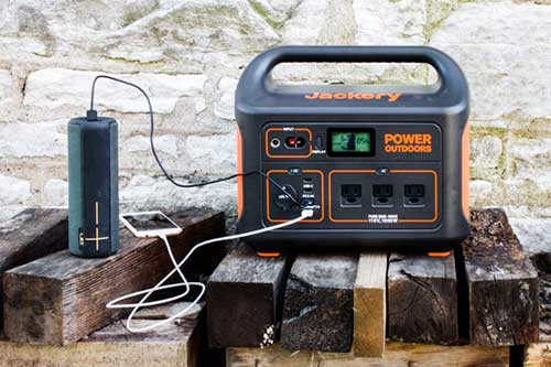 Portable Power Station Charging an iPhone and a Bluetooth Speaker