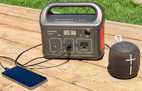 Smartphone and a Bluetooth Speaker plugged into Portable Power Supply for Camping